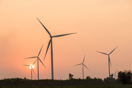 wind mill: silhouette of wind turbines power generator at sunset Stock Photo