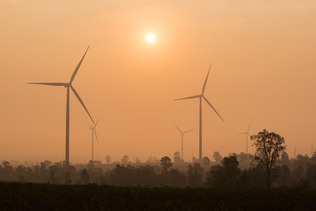 conservation: silhouette of wind turbines power generator at sunset Stock Photo
