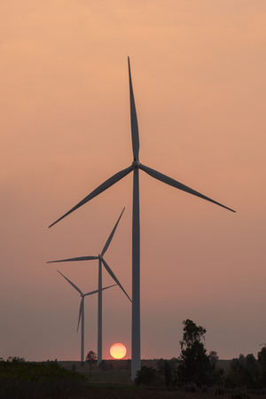 renewable energy resources: silhouette of wind turbines power generator at sunset Stock Photo