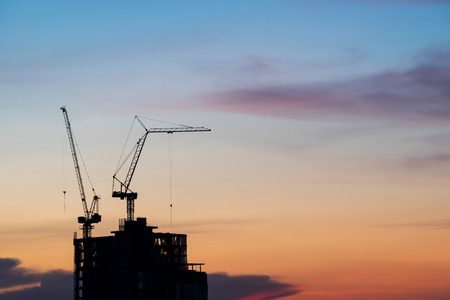 crane tower: silhouette of crane and building construction at sunset