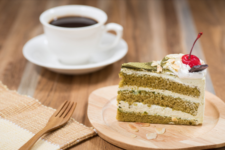 green tea cake on wooden table with a coffee cup