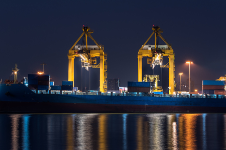 delivery truck: container cargo freight ship with working crane bridge in shipyard at night for logistic import export
