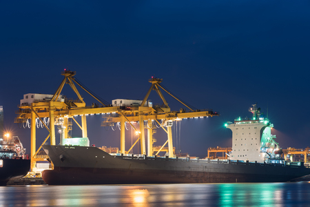 unloading: container cargo freight ship with working crane bridge in shipyard at twilight for logistic import export