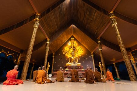 UBON RATCHATHANI, THAILAND - February 18, 2019: Group of buddhist monks are chant at night before Makha Bucha Day at Wat Phu prao or Sirindhorn Wararam Phu Prao Temple or called glow temple on February 18, 2019, Sirindhorn district, Ubon Ratchathani, Thai