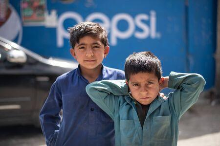 BESHAM, PAKISTAN - April 15, 2018: Unidentified unsmiling children Standing by the street near Besham, Pakistan