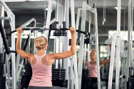 Starke junge Frau, die mit Pulldown-Maschine in einem Fitnessclub trainiert und Übungen im Fitnessstudio macht