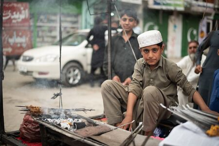 BESHAM, PAKISTAN - April 15, 2018: Unidentified children selling grilled meat on the street market