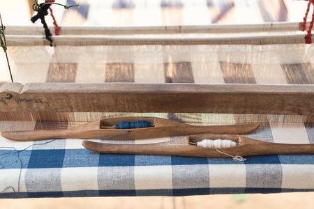Shuttle-Webwerkzeug auf dem antiken Webstuhl und Faden, traditionelle thailändische Webmaschine, Textilproduktion