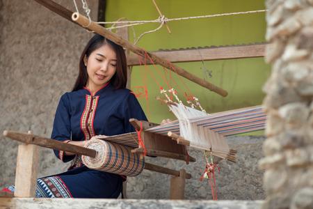 Jeunes femmes asiatiques tissant avec une machine à tisser traditionnelle thaïlandaise