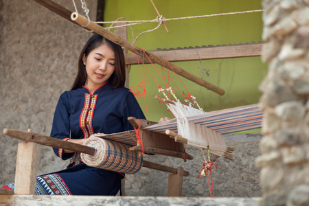 Young Asia women weaving with traditional Thai weaving machine