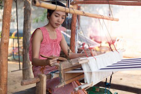 Junge asiatische Frauen, die mit traditioneller thailändischer Webmaschine weben