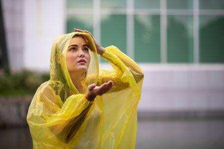 Portrait of the women wearing yellow raincoat while raining in rainy season