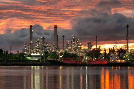 Pipelines and towers of oil and gas refinery petrochemical factory at sunset, petroleum and chemical plant