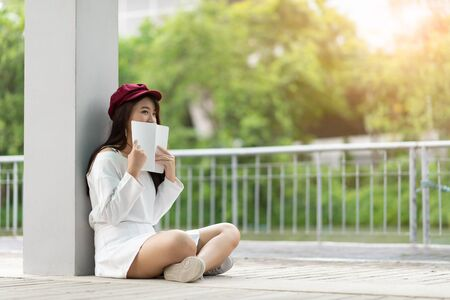 Portrait of happy young Asia woman reading storybook on couch at home, lifestyle smiling people concept Zdjęcie Seryjne
