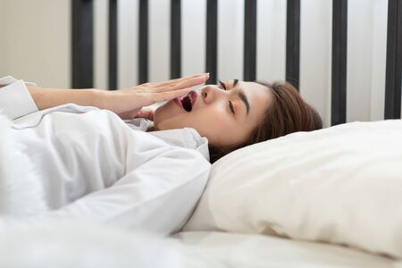 Young Asian woman yawning because she is tired while waking up in the morning