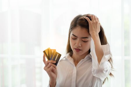 Portrait of Young Asian woman holding credit card with feeling stressed