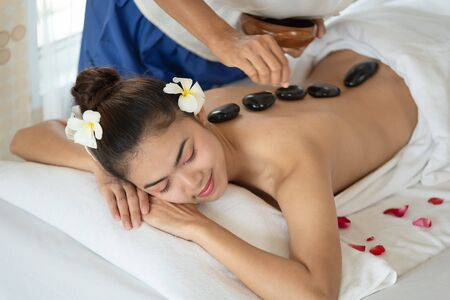 Young Asian woman lying down on massage bed with traditional hot stones along the spine in spa salon, enjoying and relaxing time Stockfoto