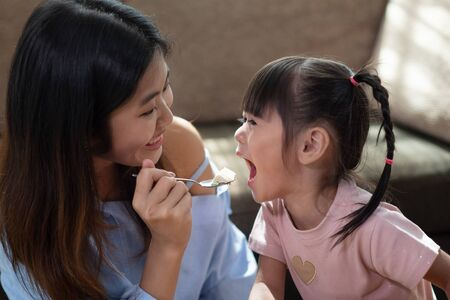 Portrait of happy Asian woman feeding her younger sister with spoon of tasty cake