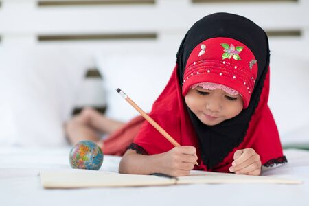 Young muslim girl writing a book, little islamic child do homework at home Фото со стока