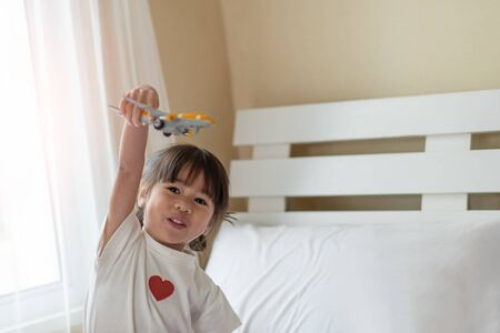 Happy Asian child enjoy playing with toy airplane in hands, dreams and imagination of children concept Imagens