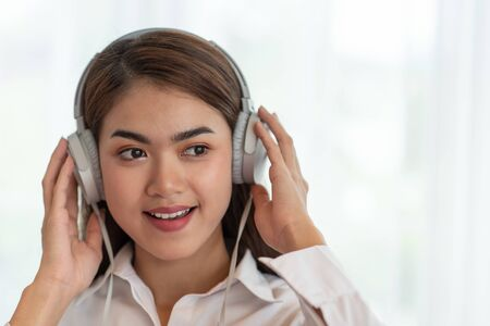 Portrait of Young Asian woman enjoy listening to music with headphones, happy and relaxing time Banco de Imagens