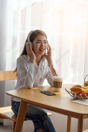 Portrait of Young Asian woman enjoy listening to music with headphones and a hot cup of coffee on the table, happy and relaxing time