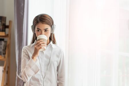 Portrait of Young Asian woman enjoy listening to music with headphones and holding a hot cup of coffee, happy and relaxing time