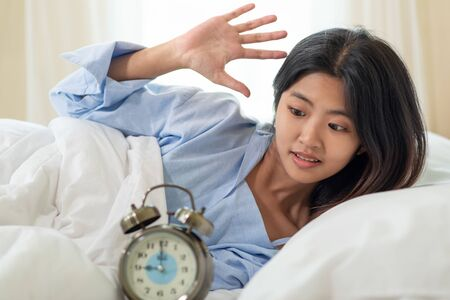 Portrait of young Asian woman shocked as she waking up late in morning, young girl laying in bed Stock Photo