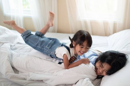 Happy Asian family loving children, kid and her sister relaxing together in bed, love and happiness concept Stock Photo