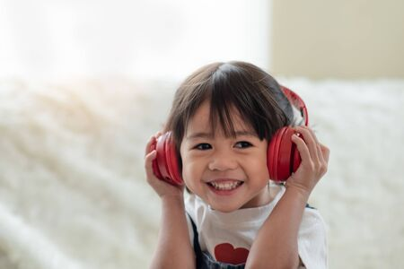 Portrait of happy Asian child enjoy listening to music with headphones