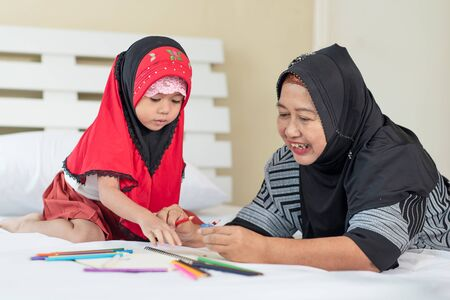 Young muslim girl hand using pencil sharpener for sharpening colored pencils with grandma, education concept