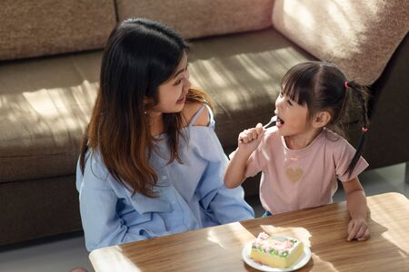Happy Asian child enjoy eating tasty cake with her older sister, love and happiness family concept