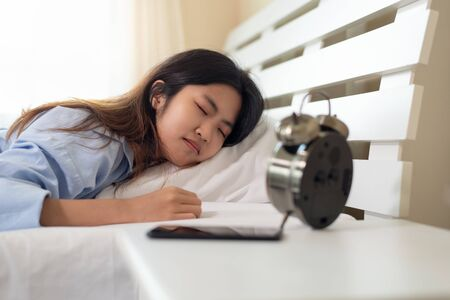 Young Asian woman sleeping in her bed with alarm clock on the table Banco de Imagens