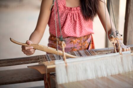 Close-up of women's hands weaving with traditional Thai weaving machine Banque d'images