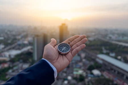 Businessman holding a navigation compass in hand and define marketing direction