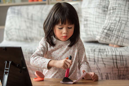 Asian child learning make up on her skin with brush by themselves, make-up artist concept