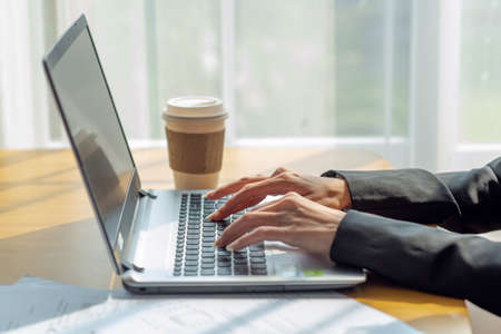 Close up of a businesswoman hands typing in a laptop in the office with cup of coffee, business concept