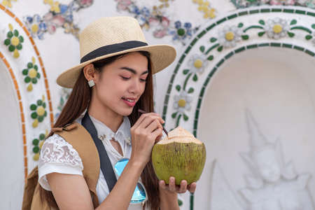 Young Asian women tourist holding coconut and traveling at Wat Arun Ratchawararam (the Temple of Dawn), one of the famous places in Bangkok, Thailand