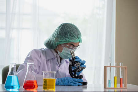 Young Asian women scientist looking through a microscope in a laboratory, Science and chemistry concept, Medical technologist