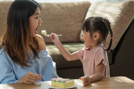 Portrait of happy Asian younger sister feeding her older sister with spoon of tasty cake