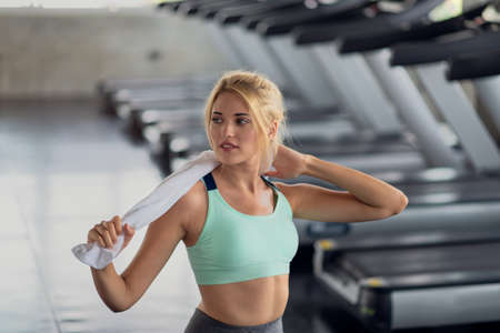 Portrait of happy woman staying with a towel after workout in the gym, Fitness and healthy lifestyle concept