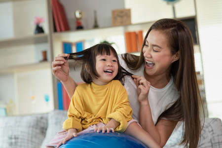 Mother having fun and playing with her daughter at home, Happy Asian little child, family concept Archivio Fotografico