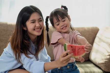 Happy Asian child enjoy eating a ripe juicy watermelon with her older sister, love and happiness family concept