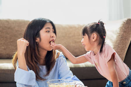Happy Asian child enjoy eating popcorn with her older sister, love and happiness family concept Standard-Bild