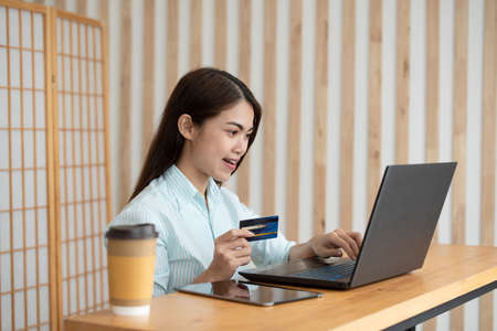 Young Asian woman holding credit card and using laptop for online shopping