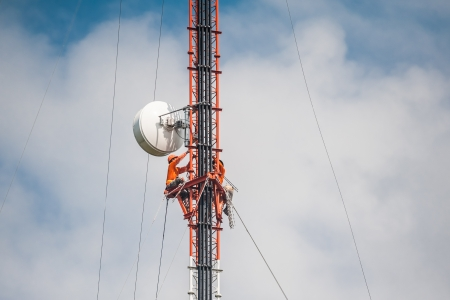 electric cell: Tower climber and working on cellular tower system. Stock Photo