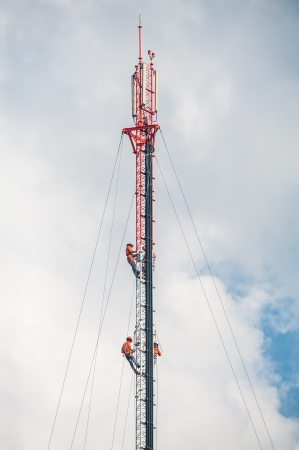 Tower climber and working on cellular tower system. photo