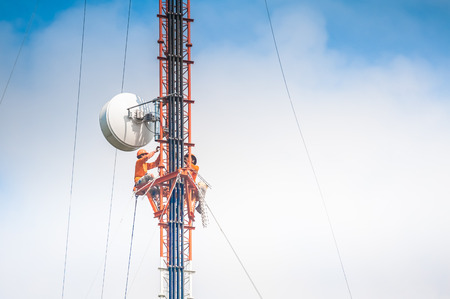 harness: Tower climber and working on cellular tower system. Stock Photo