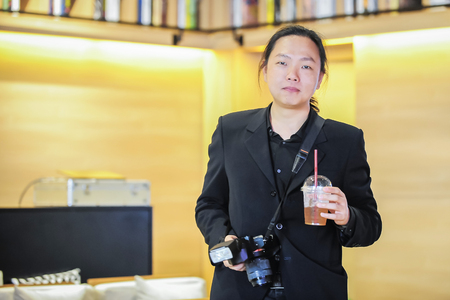 Relaxing Asian photographer holding beverage and camera
