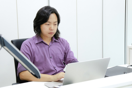 Asian long hair guy focuses and concentrates on his work in front of laptop in the office.